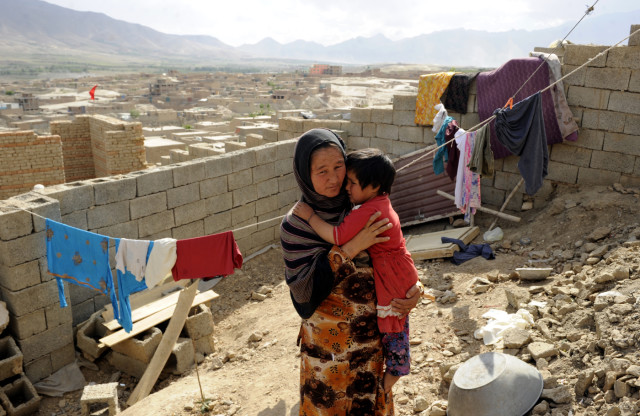 An Afghan returnee Sadiqa, 30, holds her daughter in her shetter yard in Kabul, Afghanistan, June, 11, 2012. Sadiqa and her family returned to Afghanistan 7 years ago after living for 5 years in Pakistan and are building their home by the support of Norwegian Refugee Council shelter programs in Afghanistan.   Norwegian Refugee Council shelter program in Afghanistan targets internally displaced persons, returning Afghan refugees and host communities by providing shelter interventions include short-term emergency shelter and longer-term permanent shelter construction.  Photo by Farzana Wahidy